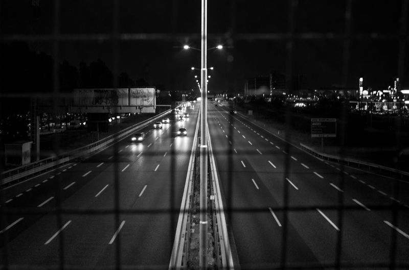 Vehicles On Highway At Night Seen From Metal Grate