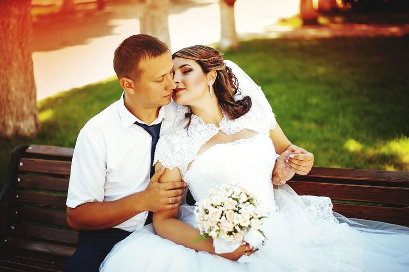 Couple sitting on bench during wedding
