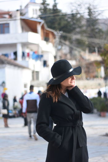 Young woman wearing hat standing against city in background