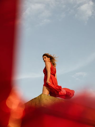 Low Angle View Of Woman Looking Away On Terrace Against Sky