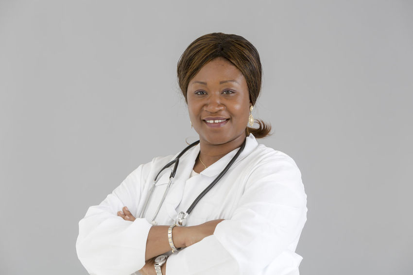 Medical Nurse Doctor  Hospital White Background Clinic Occupation Reassurance Beautiful Woman African Portrait African Girl  Stethoscope  Smiling Looking At Camera Looking To The Camera Front View Crossed Arms Selfconfident Self Confident Self Confidence Trust Reassure Reassuring Posing