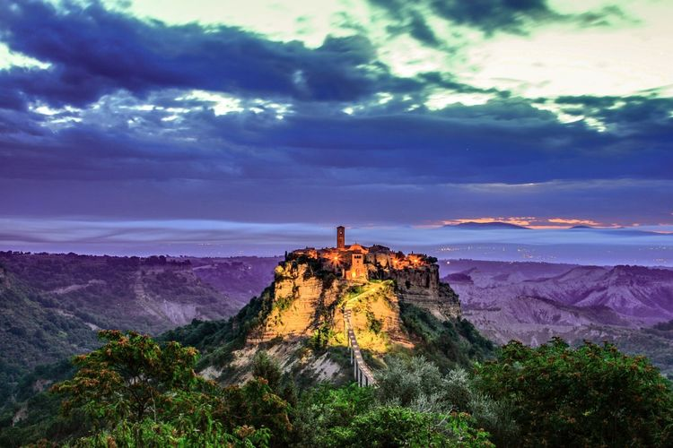 High angle view of civita di bagnoregio amidst mountains at dusk