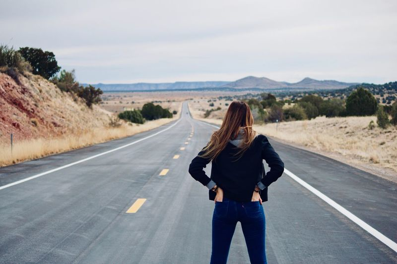 Rear View Of Woman Standing On Road Against Sky