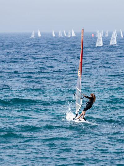 Woman windsurfing on sea