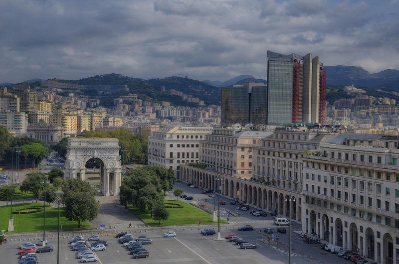 Arco della vittoria amidst cityscape against cloudy sky