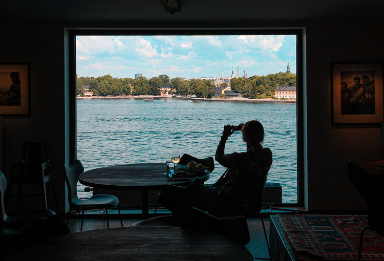 Man sitting on table by window