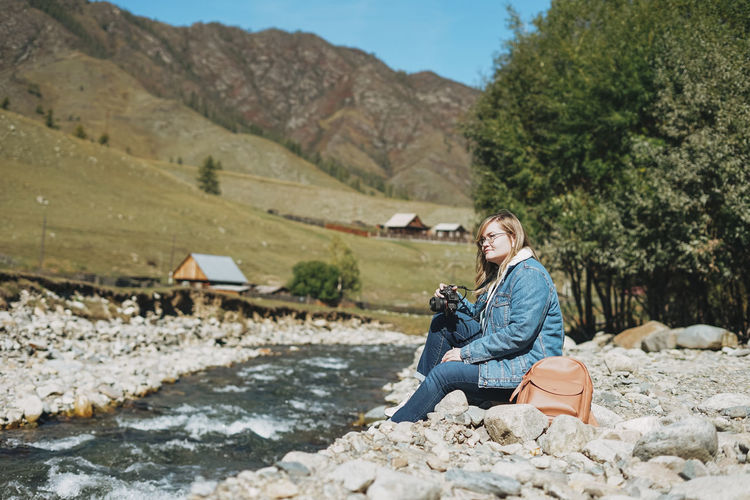Beautiful smiling blonde young woman traveler with photo camera in hands near mountain river