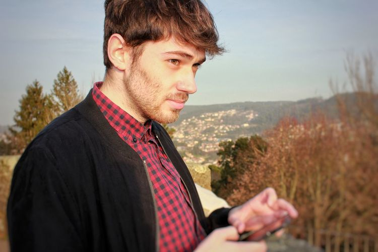 Close-up of thoughtful young man using phone while standing against sky
