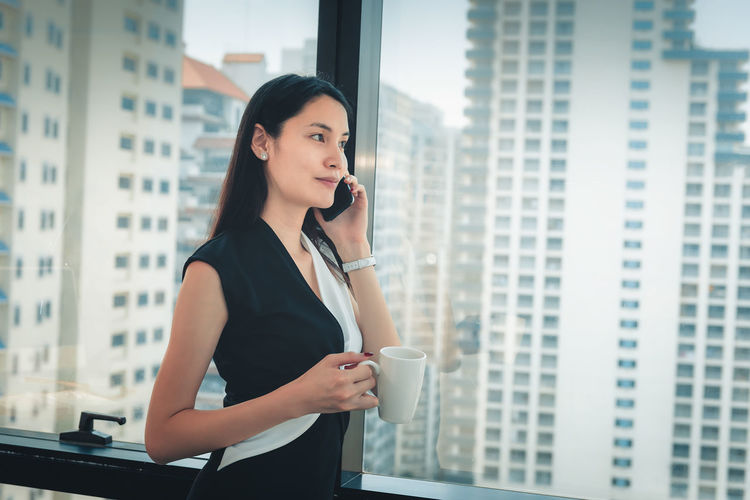 Businesswoman holding coffee cup and using phone while standing by window