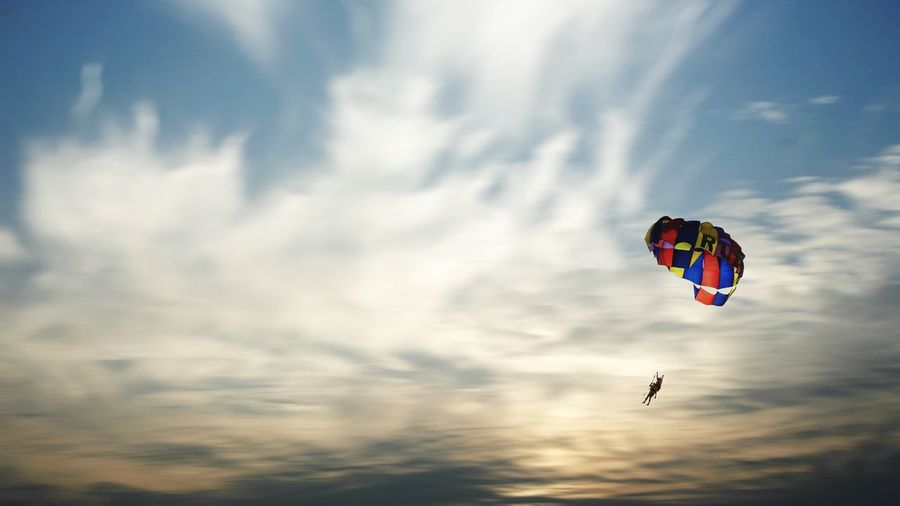 Low Angle View Of People Paragliding Against Sky During Sunset
