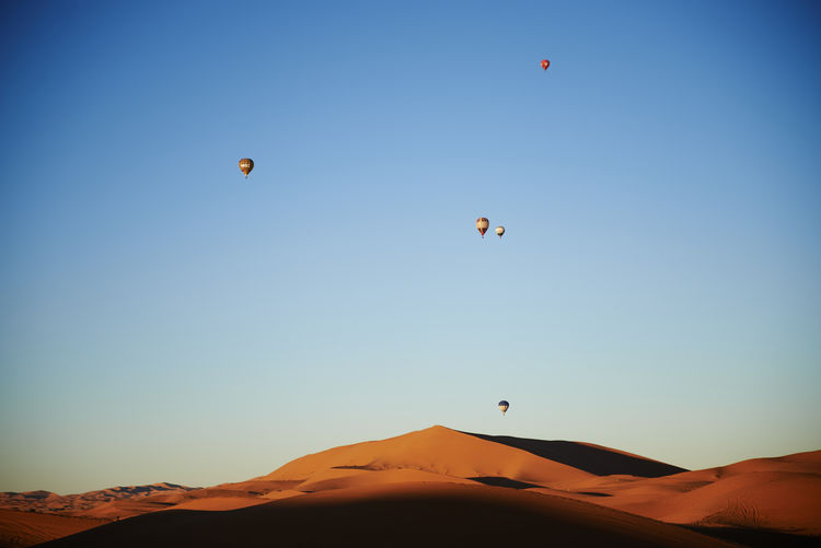Hot air balloons flying in desert against clear blue sky