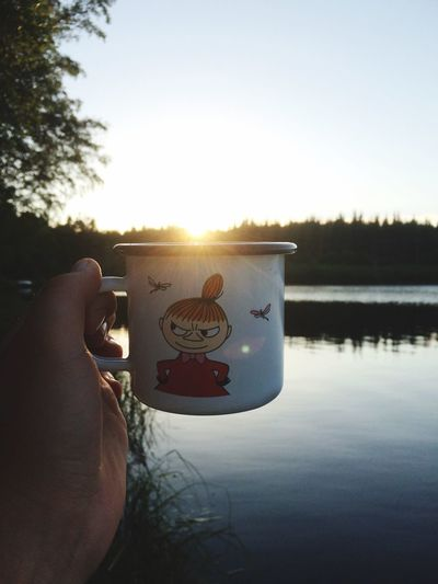 Cup of Tea? Human Hand Personal Perspective Holding Showing Water Human Body Part One Person Human Finger Real People Lifestyles Leisure Activity Men Drink Tree Sky Refreshment Sunset Sunlight Close-up Lake