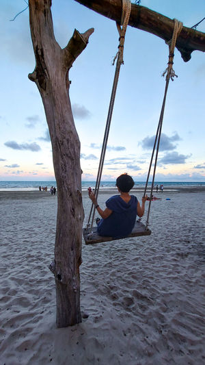 Rear view of man sitting on swing