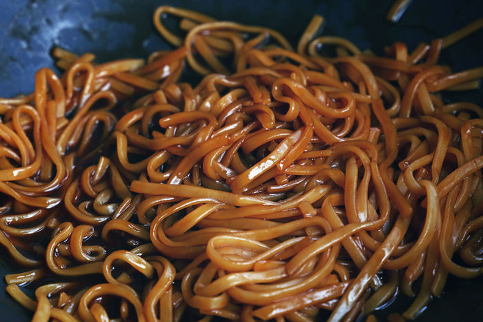 Close up of Asian udon noodles with soysauce in wok frying pan Chinese Food Cooking Cuisine Culinary Eating Meal Noodles Udon Noodles Asian Food Close-up Food Freshness Fried Healthy Eating High Angle View No People Oriental Personal Perspective Soy Sauce Stir Fry Thai Food Udon Wok Food Stories