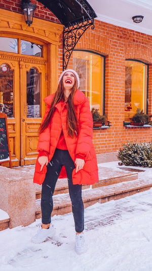 Beautiful woman standing against building during snowfall in city
