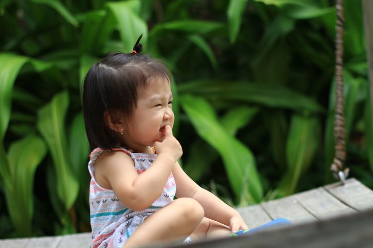 Cute girl with finger in mouth sitting on swing at park