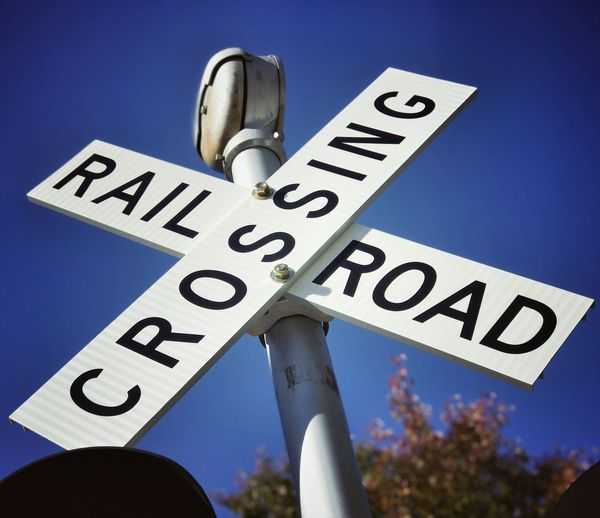 Railroad crossing signals Text Communication Low Angle View Blue Sky Road Sign Outdoors Day Close-up No People Railroad Track Railroad Railroad Crossing Signs