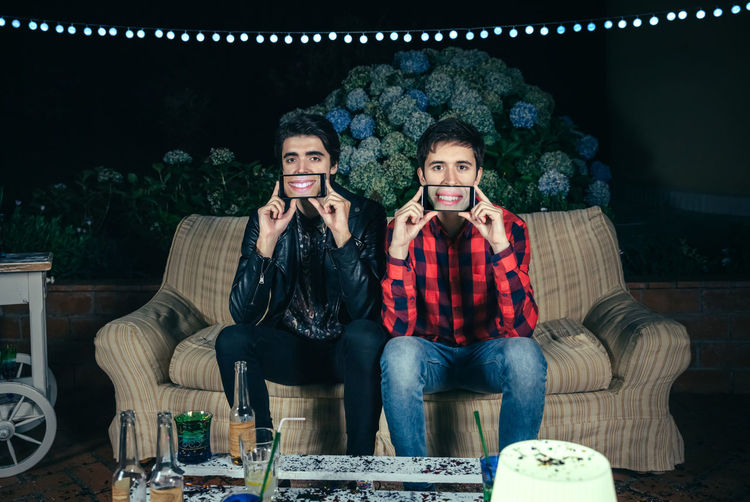 Close up of two funny young men holding smartphones showing female mouths smiling in the screen on a outdoors party Celebration Fun Funny Garland Horizontal Lips Man Mouth Screen Sitting Caucasian Covering Display Female Grimace Male Night Outdoors Party Phone Smartphone Smiling Sofa Togheter Two People