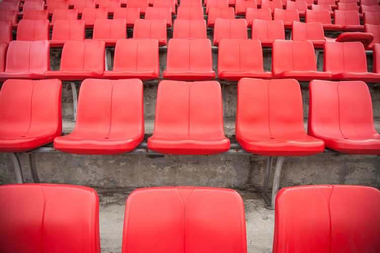 Red empty chairs in row at stadium