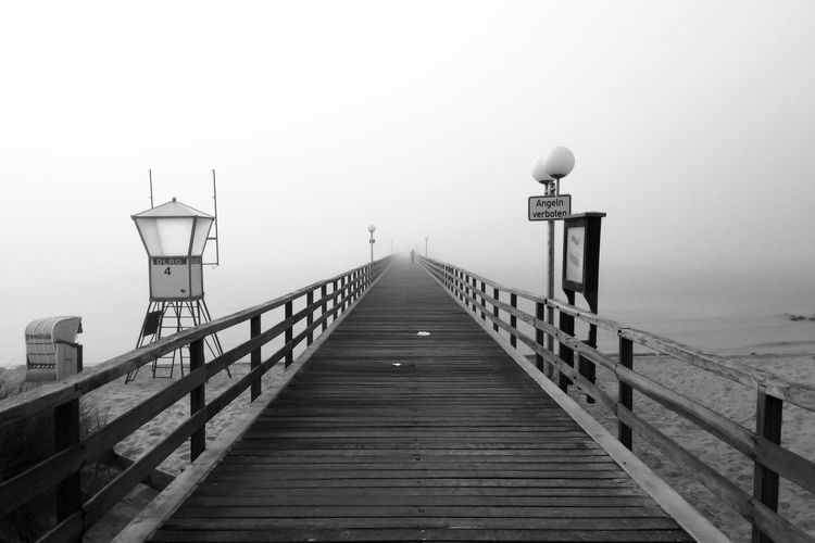 Pier amidst sea against sky during foggy weather
