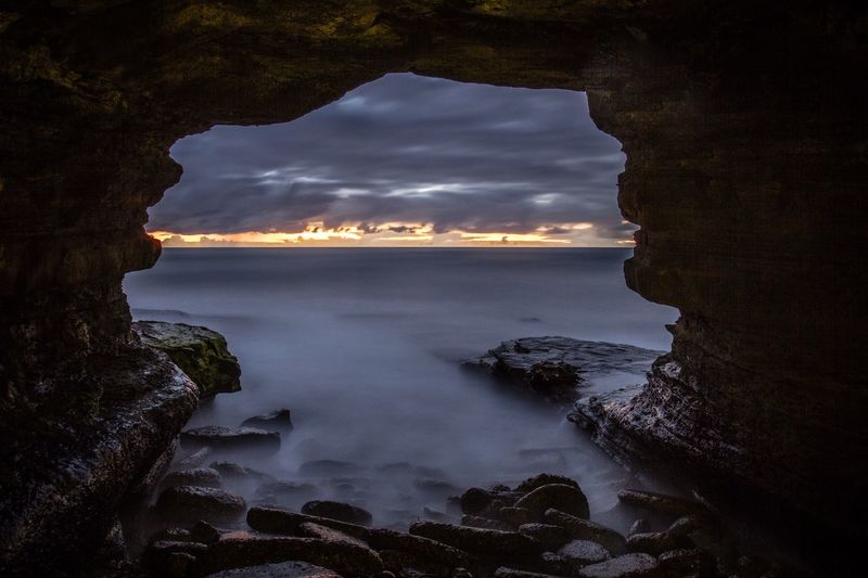 Scenic view of seascape against cloudy sky seen through cave during sunset
