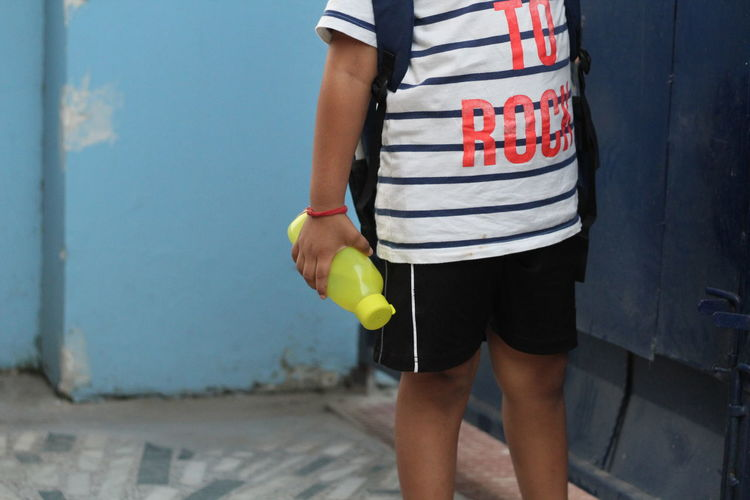 Midsection Of Boy Holding Water Bottle While Standing Against Wall