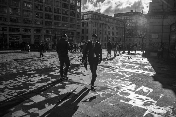 People walking on street in city during sunny day
