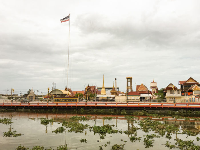 Thai Flag At Temple By River Against Cloudy Sky