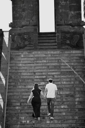 Rear view of couple walking on building
