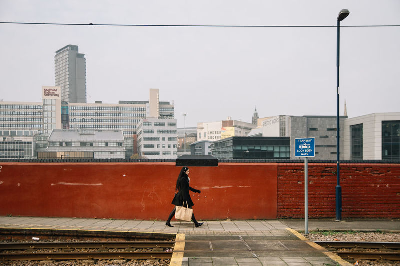 Woman Walking By Tramway In City Against Sky