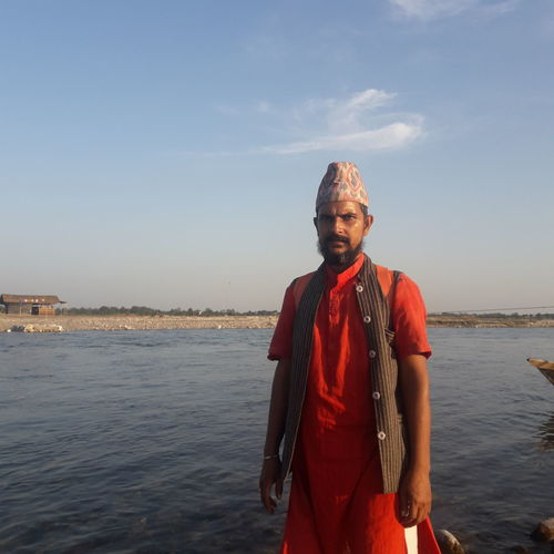 Portrait of man wearing traditional clothing standing against sea