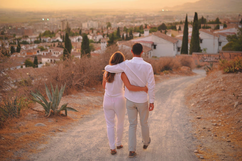 Full length of young couple on dirt road in city at sunset