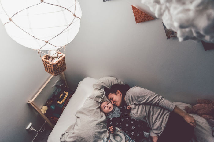 High angle view of mother and son lying on bed at home