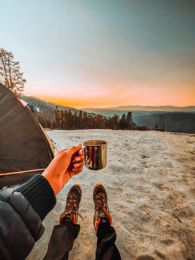 Low section of person holding coffee mug against sky during sunset