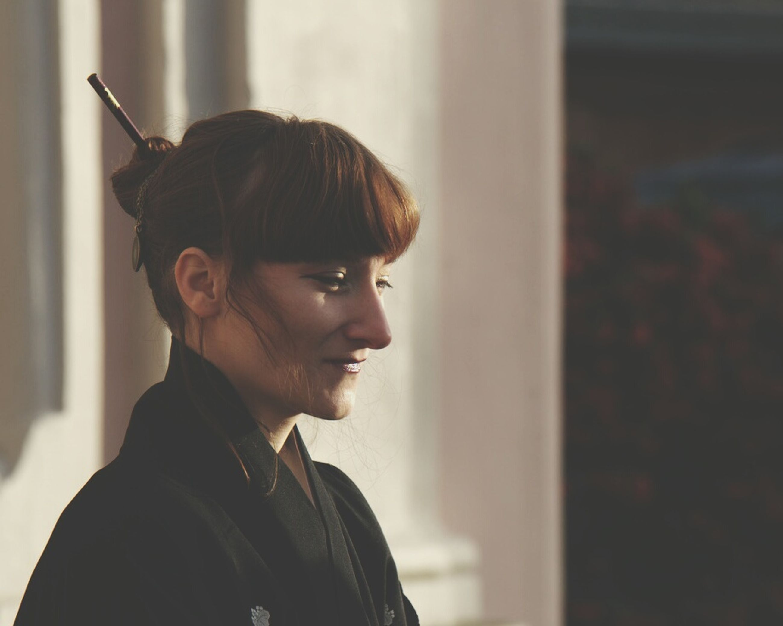 headshot, one person, portrait, side view, focus on foreground, real people, looking away, looking, young adult, indoors, hairstyle, smiling, lifestyles, standing, contemplation, young women, brown hair, bangs, beautiful woman, profile view