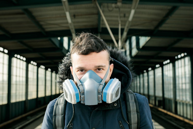 Portrait of young man at railroad station with mask on