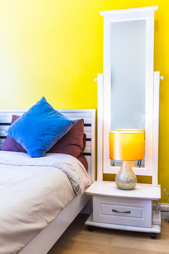 Table and yellow bed in bedroom at home