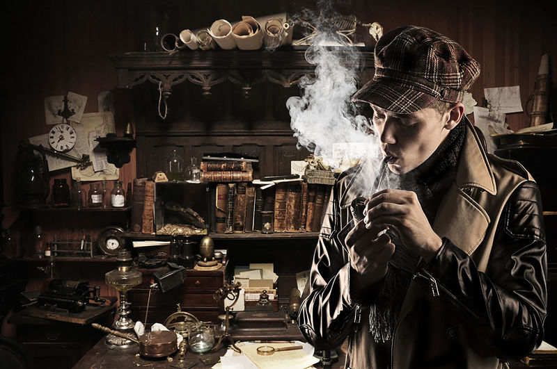 Man Smoking Pipe While Standing Against Antiques In Storage Room