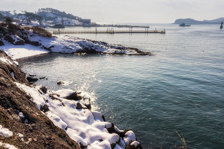 jangja island in seonyudo islands of gunsan, south korea. Snow covered coast line of the island in the winter. Coastline Korea Winter Architecture Beauty In Nature Coastal Coastal Feature Day Gunsan High Angle View Island Jeollabukdo Kunsan Nature No People Outdoors Rock - Object Scenics Sea Seonyudo Sky Snow Sunyudo Tranquility Water Shades Of Winter