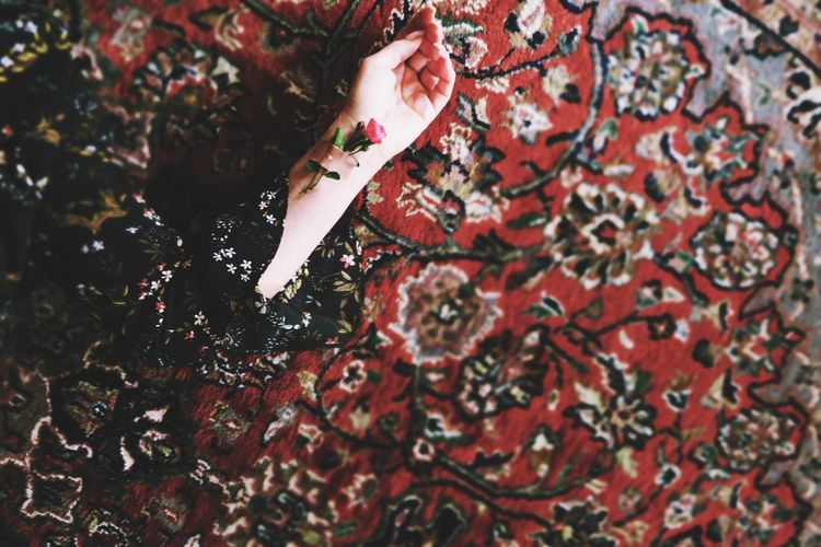 Cropped hand of woman lying on rug