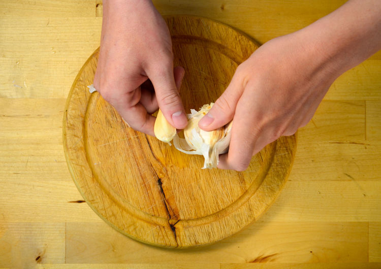 Cropped Hands Breaking Garlic Clove Over Cutting Board
