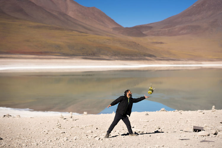Bolivia desert altiplano man playing with hat