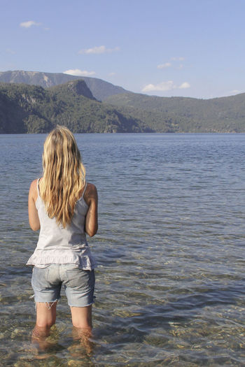 Woman Ankle Deep In Water Beauty In Nature Blond Hair Day Full Length Girl Girls Lake Leisure Activity Lifestyles Mountain Nature One Person Outdoors People Real People Rear View Scenics Sky Standing Water