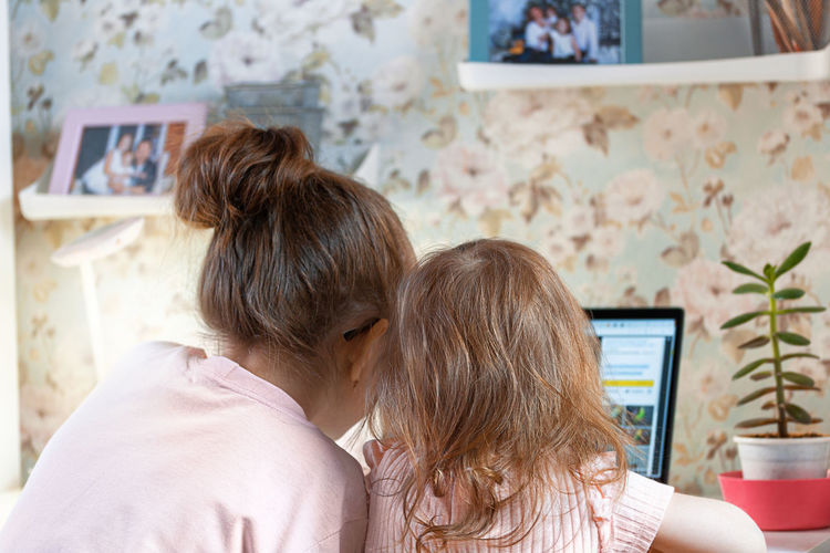 Rear view of girls using laptop at home