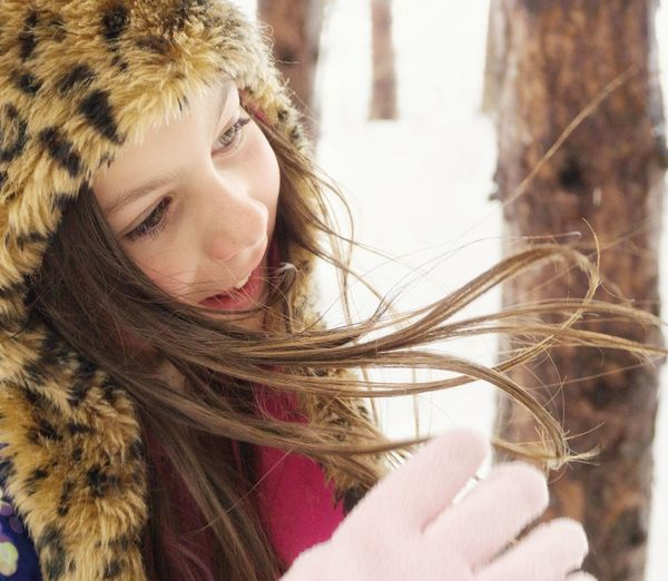 Close-up of cute girl wearing fur hat during winter