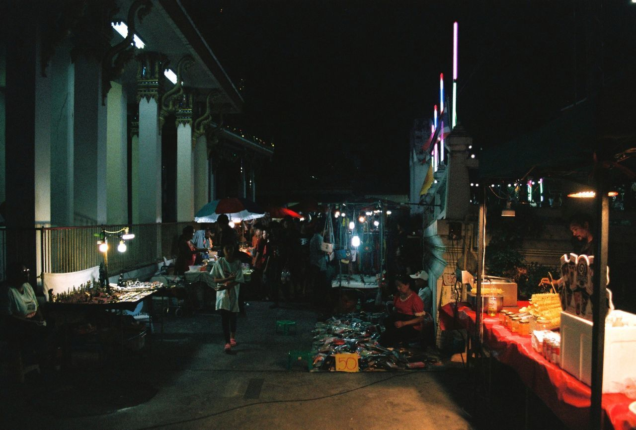 PEOPLE STANDING ON STREET AT NIGHT