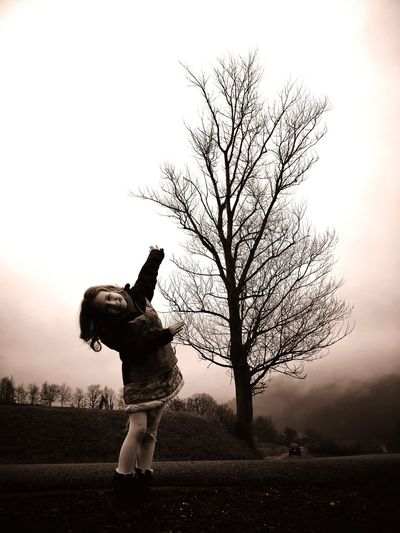 Woman standing by bare tree on field against sky