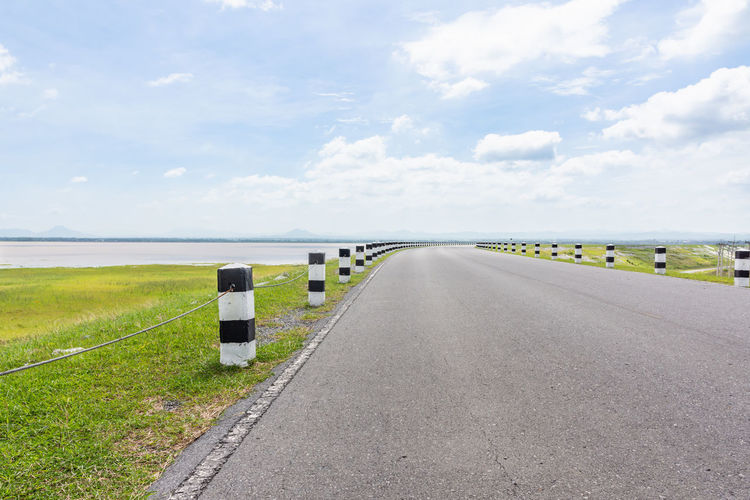 Landscape Scenic road travel on empty highway near a large reservoir with sky and clouds Sak Jolasid Dam Thailand. Beautiful Cloud Country Freedom Green Natural Nature Path Road Sunny Travel Trip View Blue Sky Empty Highway Landscape Mountain Nobody Outdoors Scenery Scenics Summer Water Way