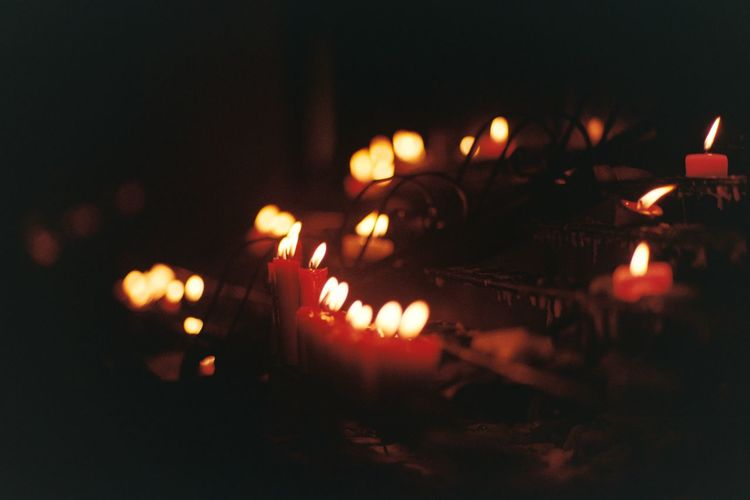 Close-up of lit candles burning at night