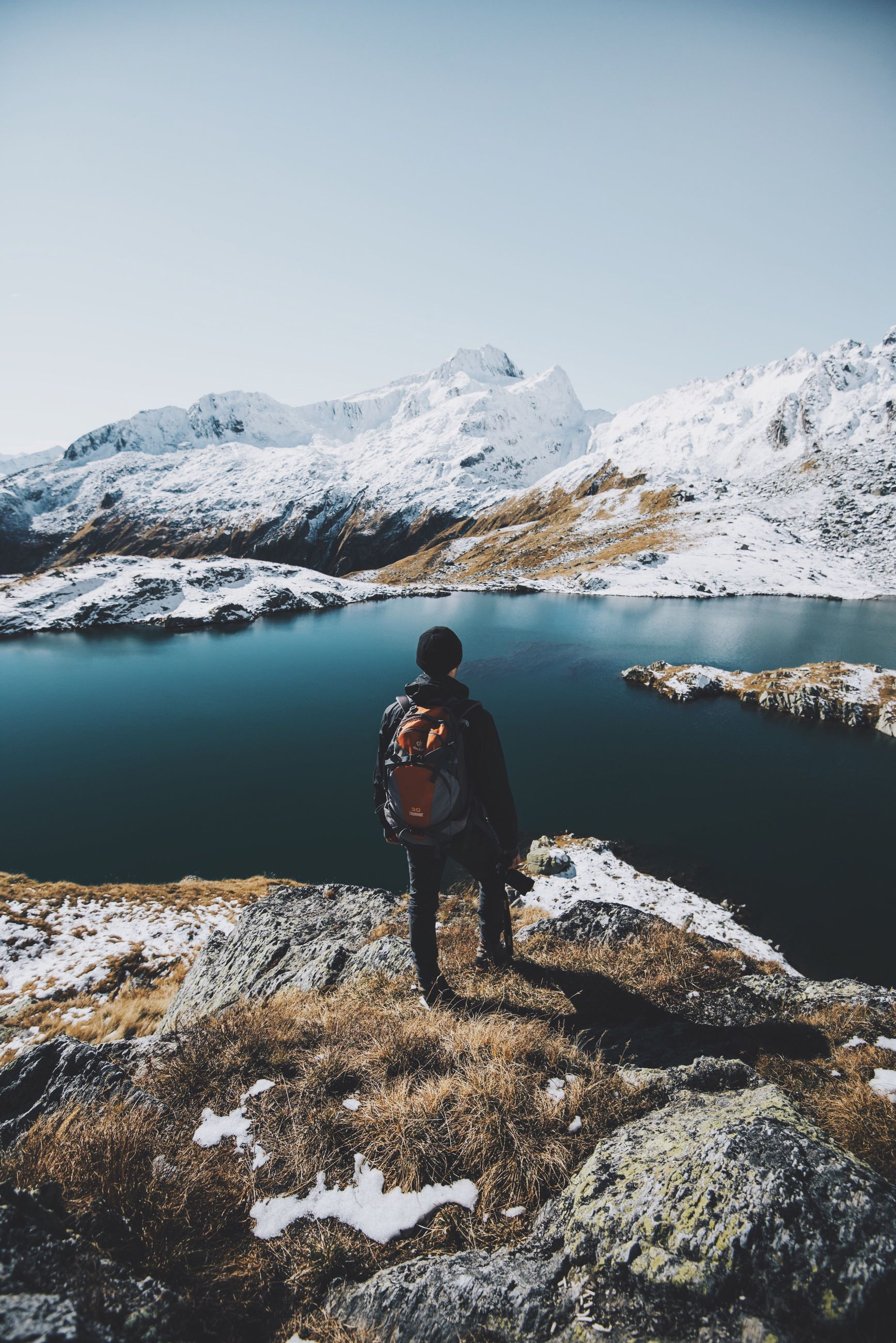 one person, beauty in nature, nature, water, real people, snow, men, leisure activity, cold temperature, mountain, winter, lifestyles, sky, outdoors, scenics, day, mountain range, lake, mammal, people